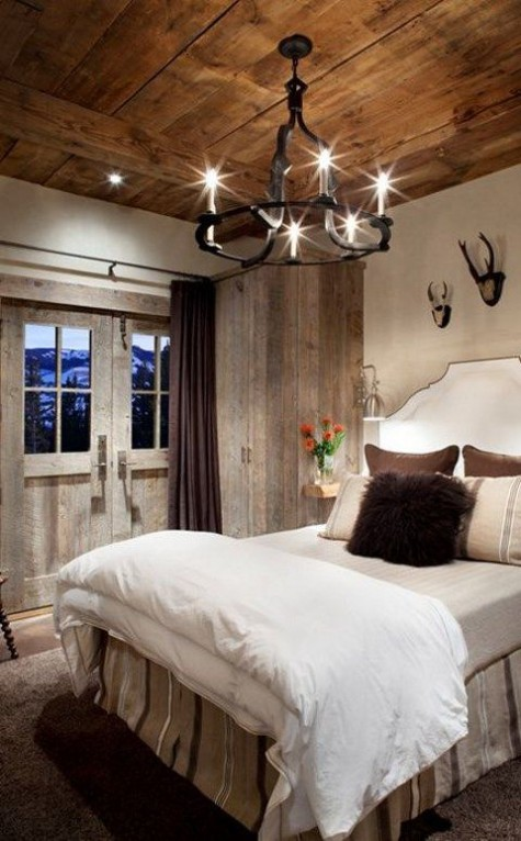 a vintage chalet bedroom done with reclaimed wood, an upholstered bed, a vintage chandelier and faux antlers on the wall