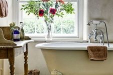 a vintage chic farmhouse bathroom with a shabby chic vanity, a free-standing tub on a platform, some blooms and a basket