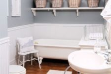 a vintage farmhouse bathroom with blue walls, beadboard, a vintage tub, a free-standing sink and baskets with blooms