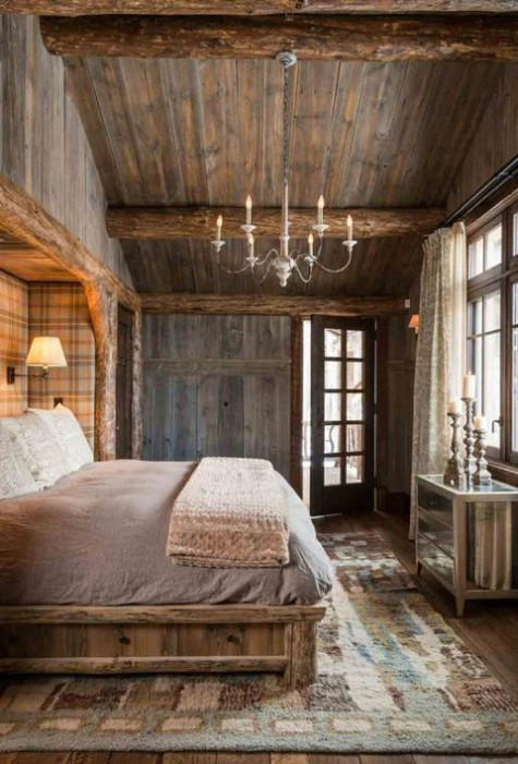 a vintage inspired chalet bedroom clad with reclaimed wood, with a wooden bed, a plaid wall, a mirror dresser