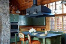 a vintage-inspired chalet kitchen clad with wood, with patina furniture, a large metal hood, an antler chandelier and vintage chairs