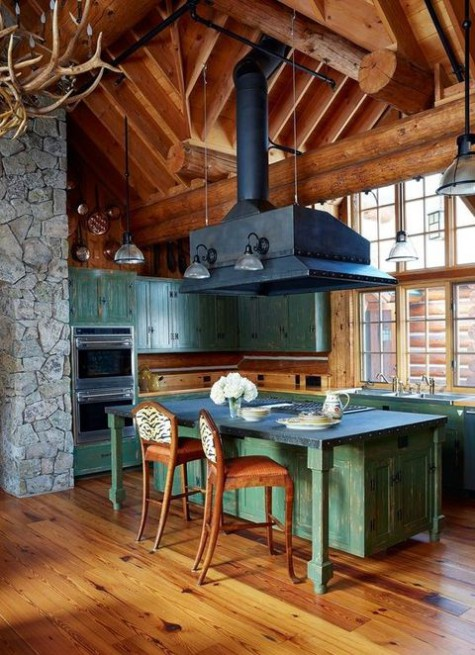 a vintage inspired chalet kitchen clad with wood, with patina furniture, a large metal hood, an antler chandelier and vintage chairs