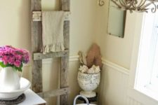 a warm farmhouse bathroom with a vintage tub, a rough wood ladder, a vintage chandelier, a vintage side table