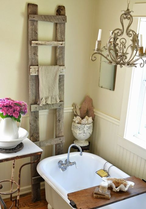 a warm farmhouse bathroom with a vintage tub, a rough wood ladder, a vintage chandelier, a vintage side table
