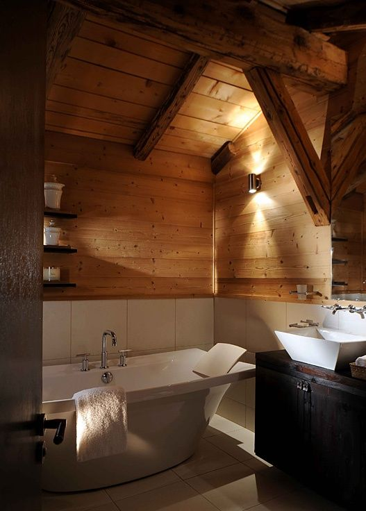 a welcoming chalet bathroom with a dark vanity, clad with wood and white tiles, with lamps and a free standing tub