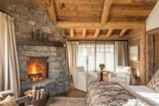 a welcoming chalet bedorom clad with wood, with a stone fireplace, faux fur and a sitting zone by the fire