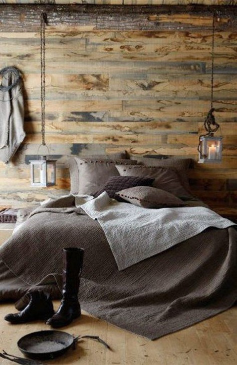 a welcoming chalet bedroom clad with light stained wood, with candle lanterns, dark bedding and some pretty decor