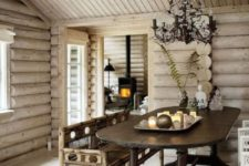 a welcoming chalet dining space clad with whitewashed wood, with vintage furniture, a vintage chandelier and some candles