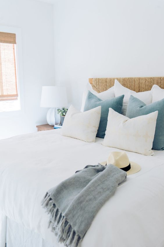 a welcoming coastal bedroom with a wicker bed, blue pillows, woodne nightstands and wicker shades