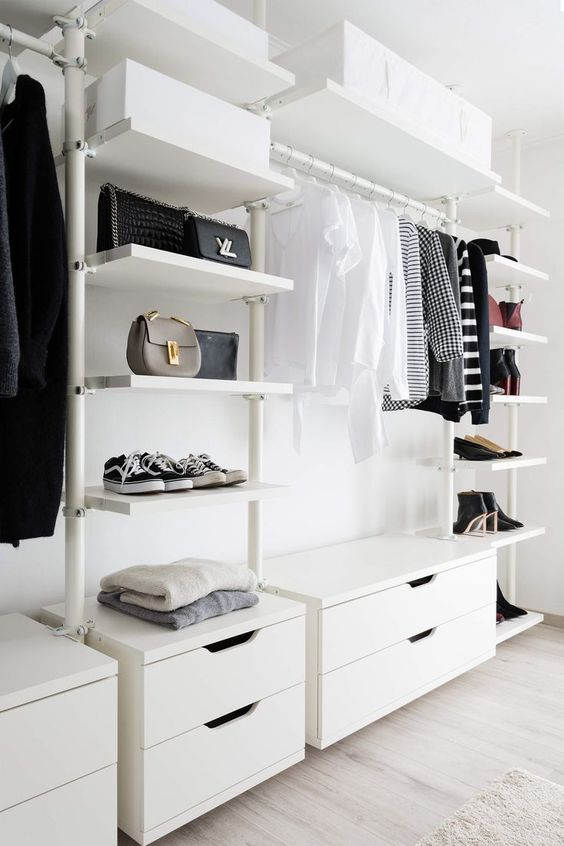 a white airy minimalist closet with drawers, open shelves, boxes and a holder for hangers