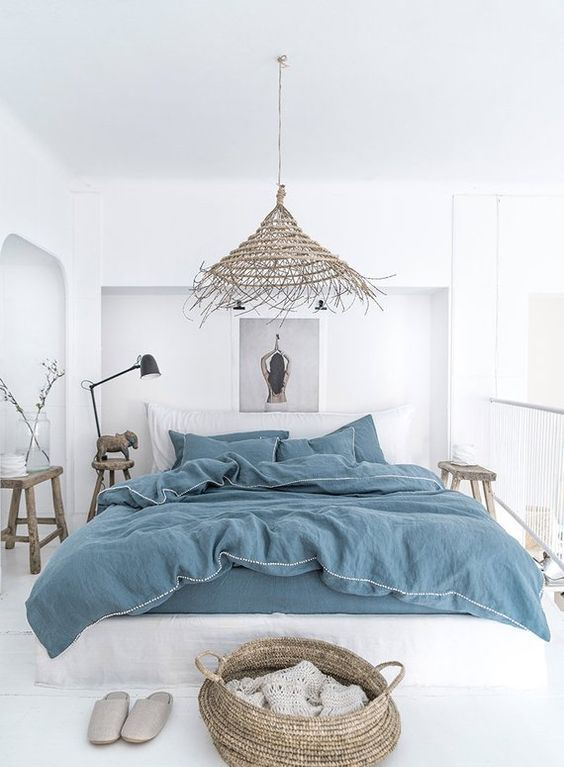 a white boho beach bedroom with all-white everything, blue bedding, baskets, a wicker lamp and wooden furniture