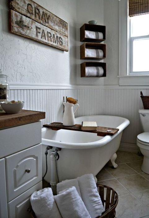 a white farmhouse bathroom with wallpaper and beadboard walls, a vintage tub, wooden box shelves and a vanity