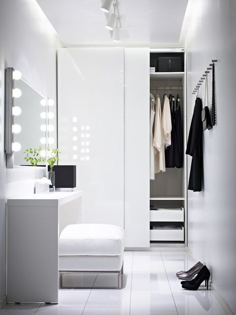 a white minimalist closet with a wardrobe with sliding doors, some hooks and a vanity with an ottoman