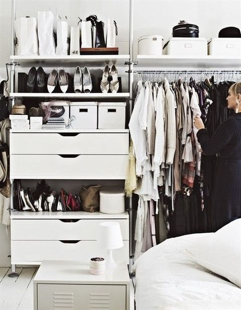 a white minimalist closet with drawers, open shelves, boxes and a holder for hangers is a cool one
