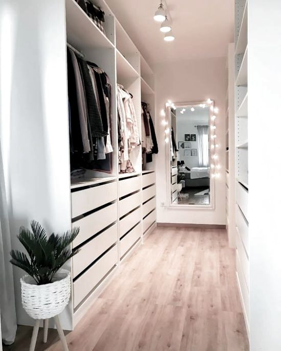 a white minimalist closet with drawers, open storage compartments and shelves plus lights and lamps