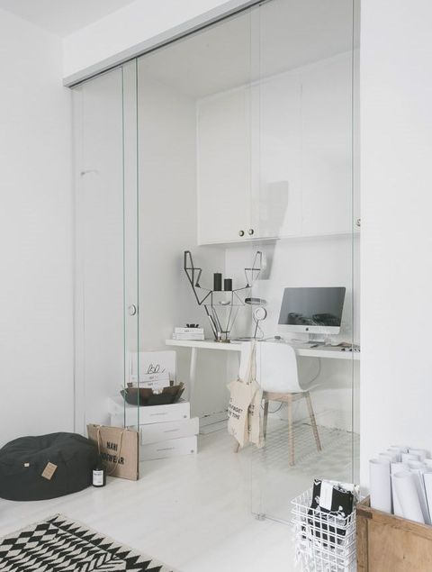 a white minimalist home office with a desk, a storage unit, a white chair and some boxes plus glass sliding doors