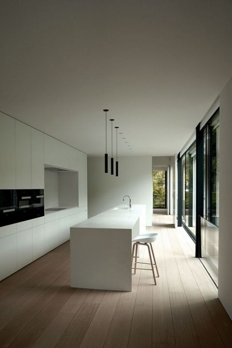 a white minimalist white with no handles, sleek cabinets, built in appliances and a white kitchen island with a meal space