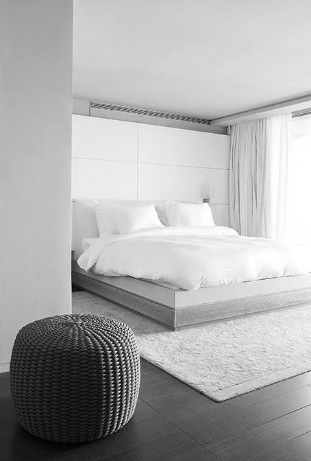 an airy minimalist bedroom with a large storage headboard, a white bed, white bedding and curtains and a wicker ottoman