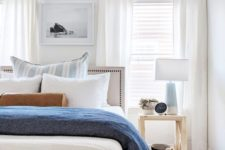 an airy modern beach bedroom with neutral walls, white curtains, blue textiles and lamps, catchy dark items
