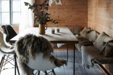 an eclectic chalet dining room with a corner bench with faux fur and pillows, a modern table and chair with fur