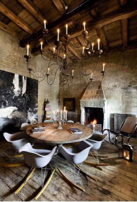 an eclectic chalet dining room with stone walls, a wooden ceiling, a vintage table and chairs on skis plus a statement artwork