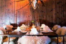 an eclectic chalet dining space with a vintage table and rustic chairs, a deer head and faux fur on the chairs