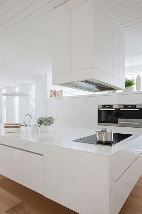 an elegant minimalist white kitchen with lots of cabinets, a large stone clad kitchen island and a large hood over it