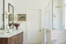 an elegant vintage farmhouse bathroom with white beadboard, a large wooden vanity and mirrors plus cool gold touches