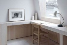 an light-filled ultra-minimalist home office with a long wooden desk, a wicker chair, lamps and a large window