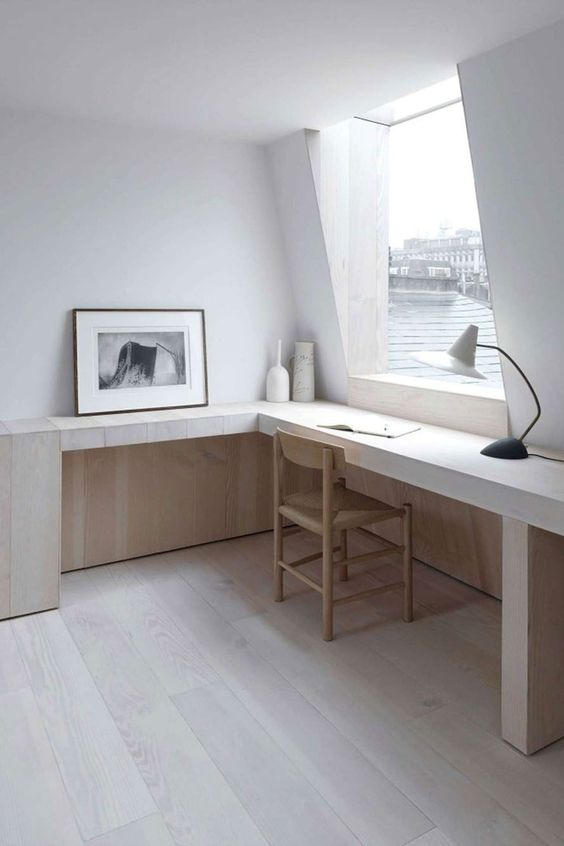 an light filled ultra minimalist home office with a long wooden desk, a wicker chair, lamps and a large window