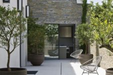 an ultra-minimalist patio with a couple of chairs, statement planters and fruit trees and greenery
