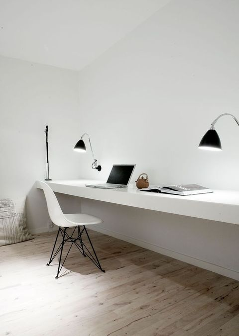 an ultra-minimalist shared home office with a white floating desk, black sconces and a white chair