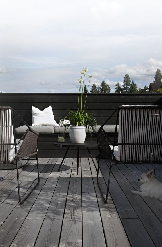 an ultra-minimalist terrace with a wooden deck, black wicker chairs, a black coffee table and some neutral textiles