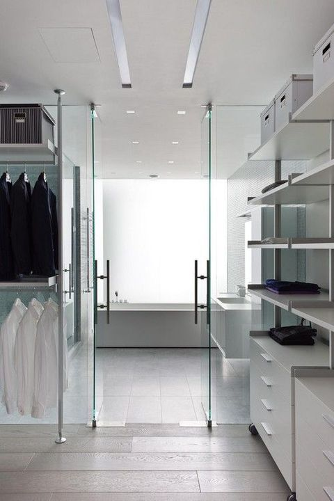 an ultra minimalist white closet with holders for hangers, open shelves and some dressers