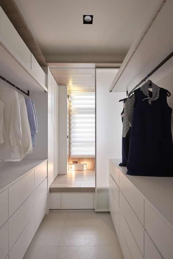 an ultra-minimalist white closet with large dressers, open shelves, holders for hangers and boxes