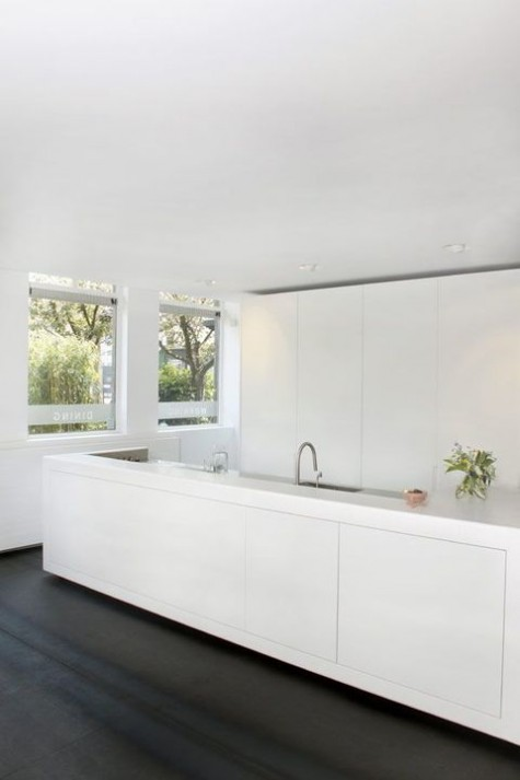 an ultra minimalist white kitchen with sleek tall cabinets and a large kitchen island plus a raised top for eating here