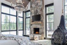 an ultra-modern chalet bedroom with a stone fireplace, a suspended chair, a catchy chandelier and lots of faux fur