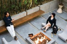 an ultra-modern patio with concrete pavements, bamboo in concrete planters and a fire pit in the center