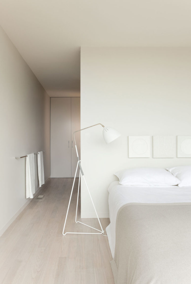 minimalist all-neutral bedroom, with closed and hidden storage, a large bed, floor lamps and neutral textiles