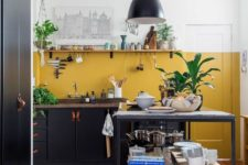 02 a black kitchen with stone countertops and a mustard color block wall for a bright touch