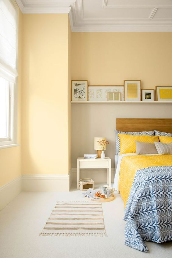 a welcoming bedroom with light yellow walls, bright yellow artworks and bedding plus printed bedding