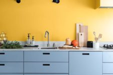 03 a chic modern kitchen with a yellow accent wall and light blue sleek cabinets that create a contrasting combo