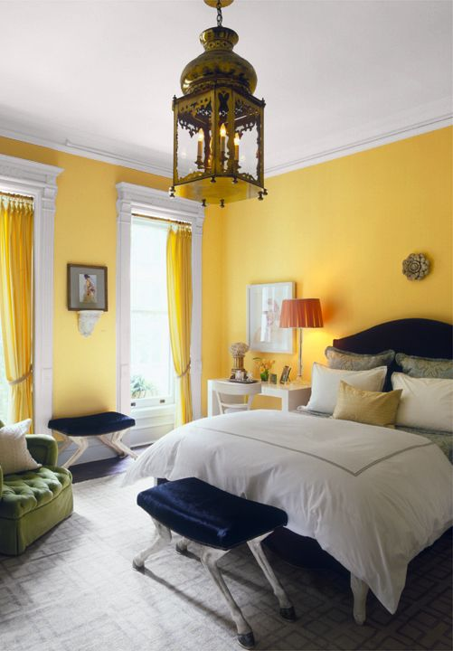 a whimsical bedroom with bright yellow walls and curtains, with navy and green furniture and a chic pendant lamp