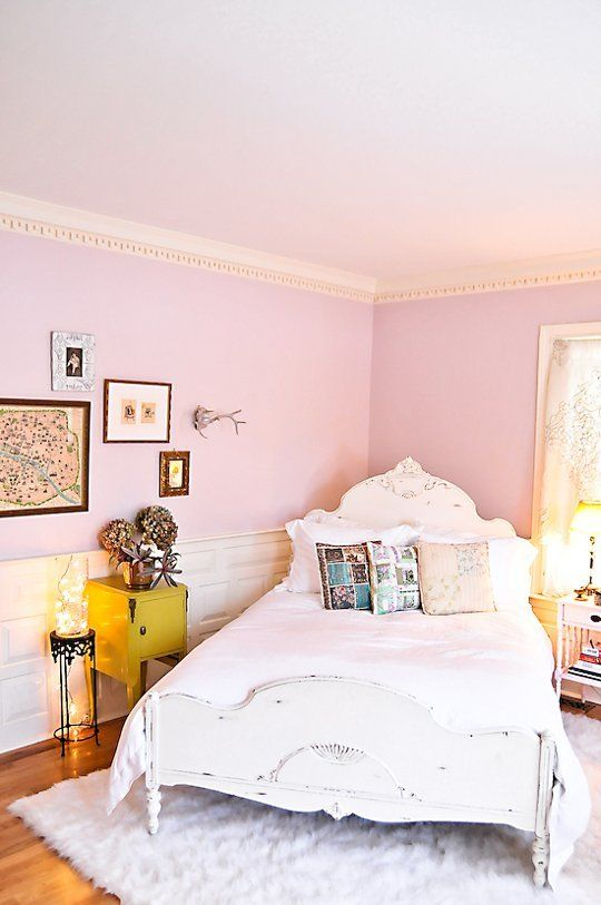 a whimsy bedroom with light pink walls, a gallery wall, a shabby chic bed and printed pillows plus lights