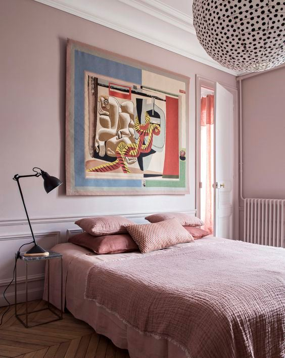 a chic bedroom with light pink walls, pink bedding and a statement artwork and a polka dot lamp