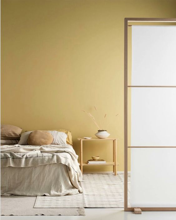 a minimalist bedroom with light yellow walls, simple wooden furniture and neutral textiles is super chic