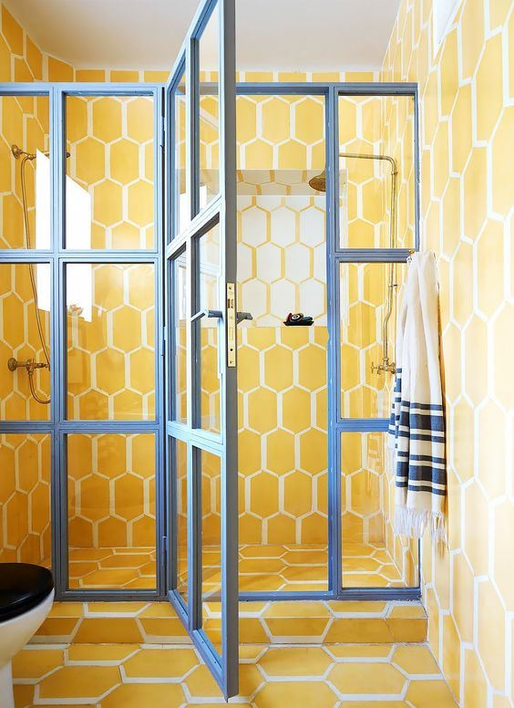 a super bright yellow tile bathroom with a glazed shower door with blue framing for a contrasting look