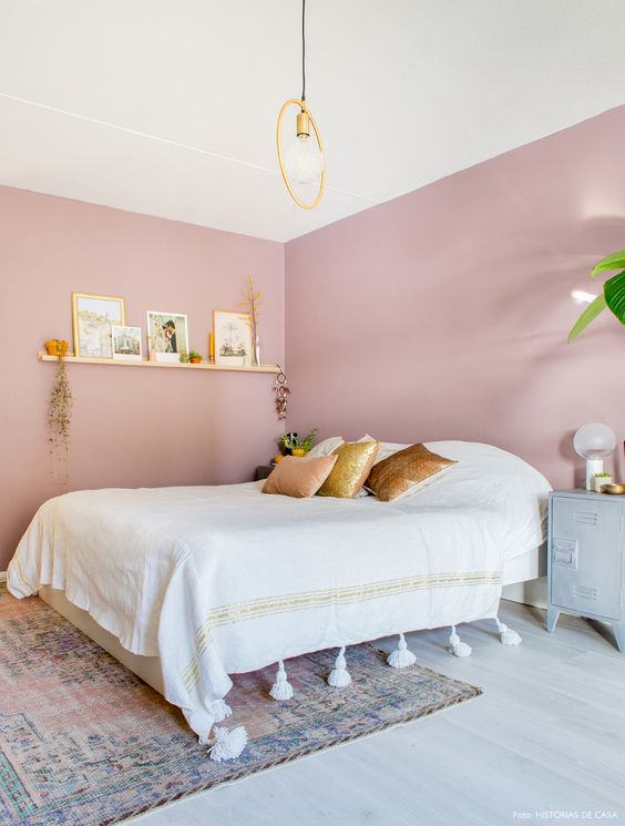 a chic and girlish bedroom with pink walls, a white bed, a floating shelf and touches of gold for more chic