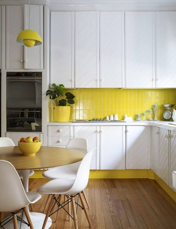 a modern white kitchen with a stripe pattern and a lemon yellow tile backsplash and a matching pendant lamp