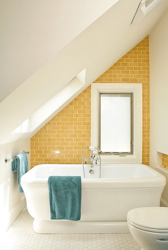 a small attic bathroom in white with a mustard tile accent wall and blue textiles is very welcoming and cool